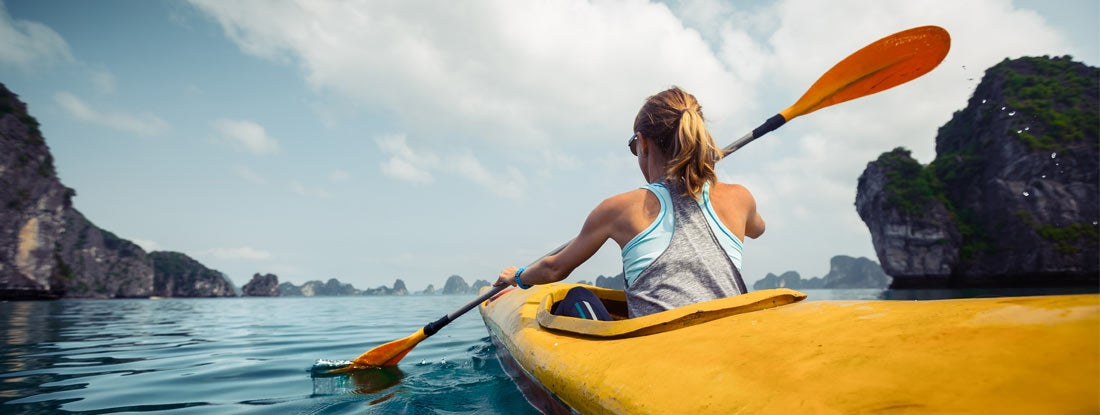 Woman exercising and exploring calm tropical bay by kayak.
