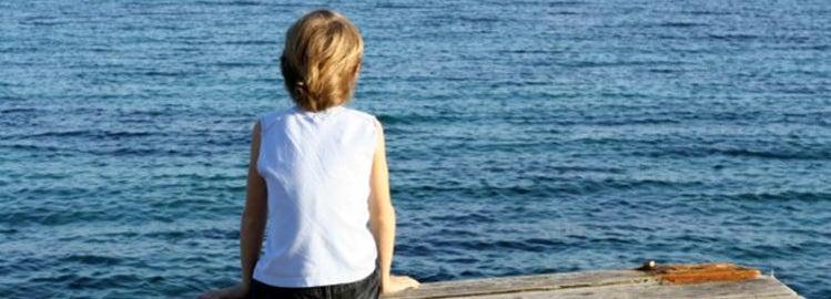 Boy sitting on a dock