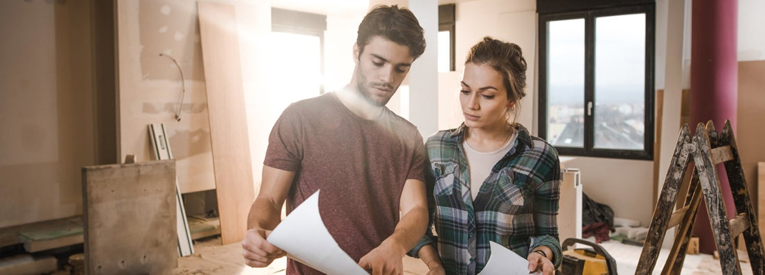 Young couple examining blueprints while being on construction site in their home