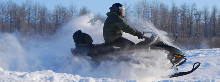 Snowmobile rider on a forest trail