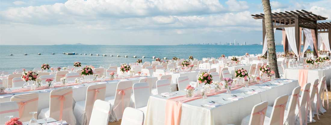 Wedding ceremony on the beach with rental tables and chairs
