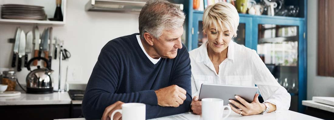 Mature couple having coffee while using digital tablet to search for a life annuity specialist