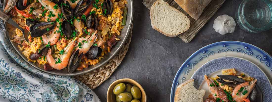Paella with olives and bread on stone table