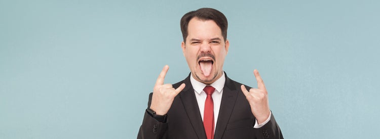 Man in suit showing tongue and rock sign
