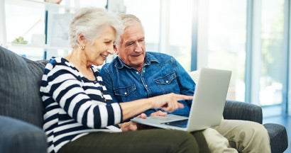 senior couple using a laptop together on the sofa at home