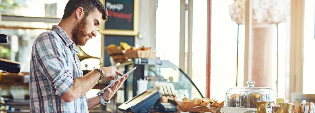 Man researching franchise restaurant insurance while working in a coffee shop