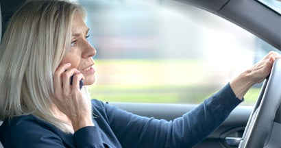 Parent driver chatting on her mobile in the car as she drives through town