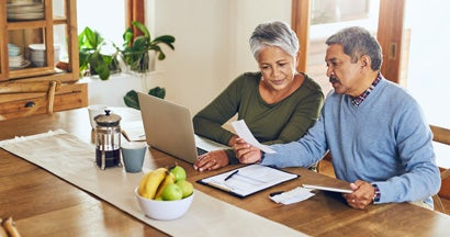 Mature couple managing their paperwork together at home