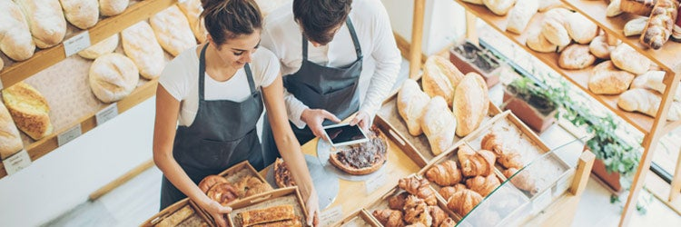Top view of young couple of bakers inside the bakery. Find bakery insurance.
