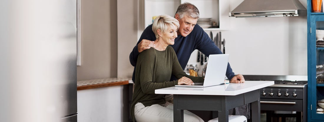 mature couple browsing fixed annuities on a laptop at home