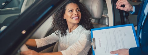 Woman in the showroom enjoying new car