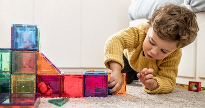 Boy playing with building blocks at home daycare