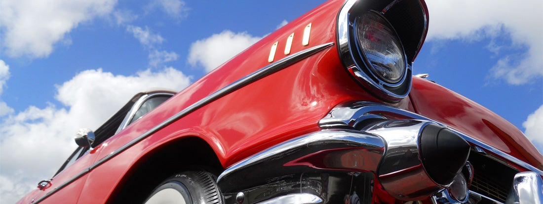 Close up of a beautifully restored 1957 Chevy Bel Air convertible, as seen at a car show.