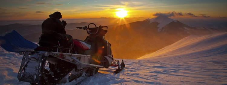 Snowmobile rider at sunset