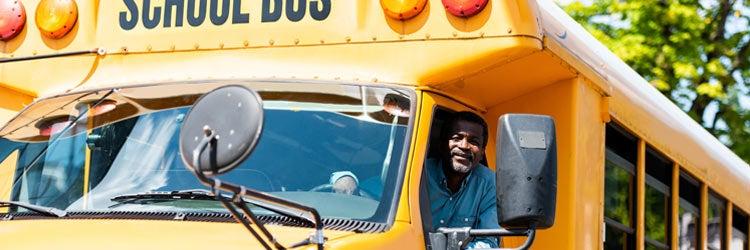 senior school bus driver looking at camera through window