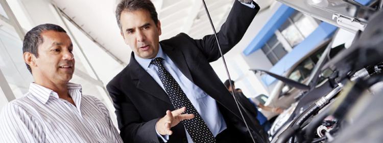Car salesman explaining something to client.