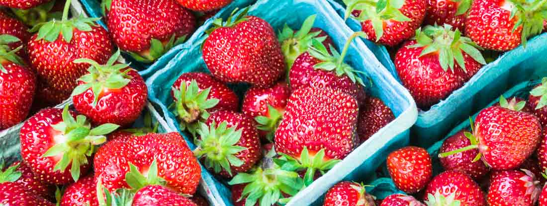 Baskets of juicy, ripe strawberries at a farmers market.