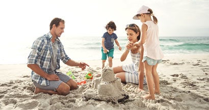 Family with young children building a sandcastle together on the beach