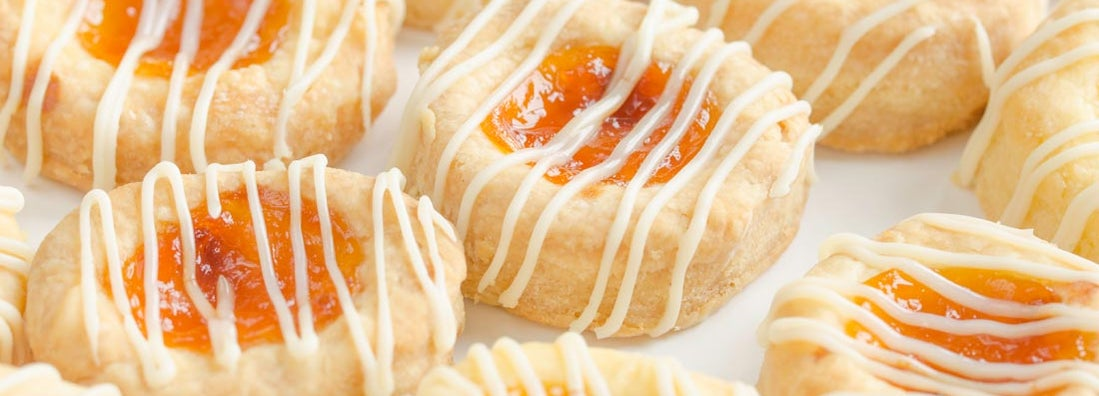 Close up of homemade cream cheese Kolache cookies filled with apricot and glazed