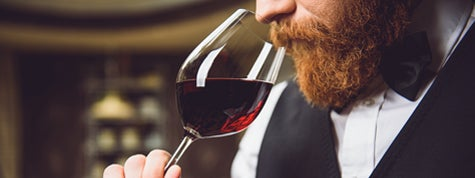 wine connoisseur is inhaling aroma of scarlet wine