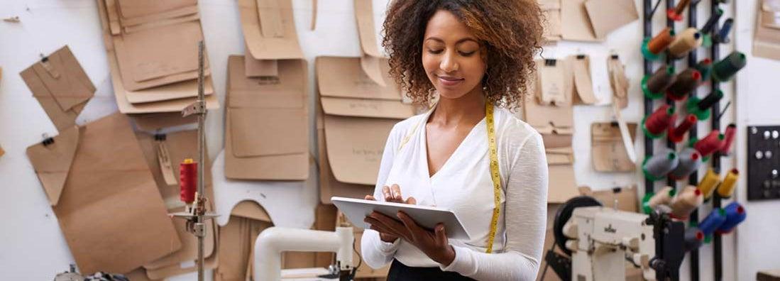 Fashion designer using her digital tablet in her workshop