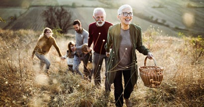 Happy senior couple leading her children and grandchildren to perfect picnic place on the hill