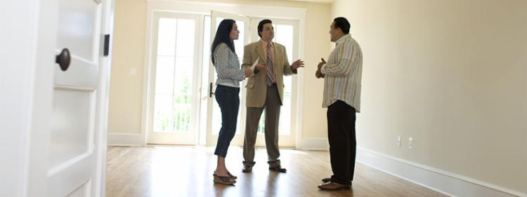 A realtor chats with potential homebuyers in an empty house.