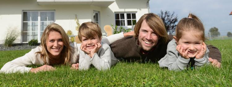 A family lays in the grass outside their new home.