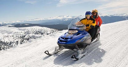 Couple riding a snowmobile