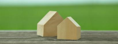 Two wooden house-shaped blocks sitting on a table.