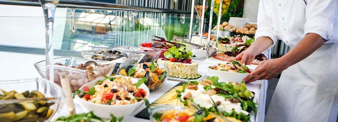 Caterer serving a large buffet table full of delicious food.