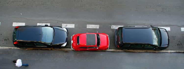 A small red car parked between two large black SUVs.