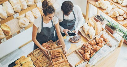 Top view of bakers inside the bakery, holding a digital tablet and arranging the pastries