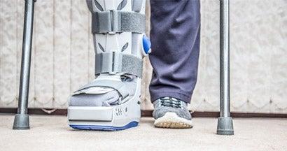 mature woman wearing leg brace and crutches