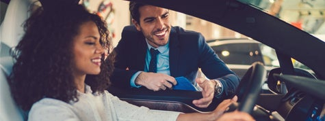 Smiling woman in the showroom enjoying luxury car