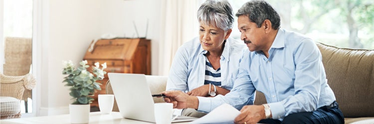 Senior couple using a laptop together at home discussing long term care insurance