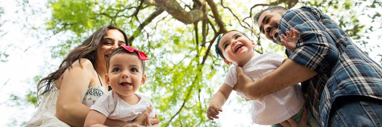 Low angle view of playful latin parents holding their twin girls and laughing in a horizontal medium shot outdoors.