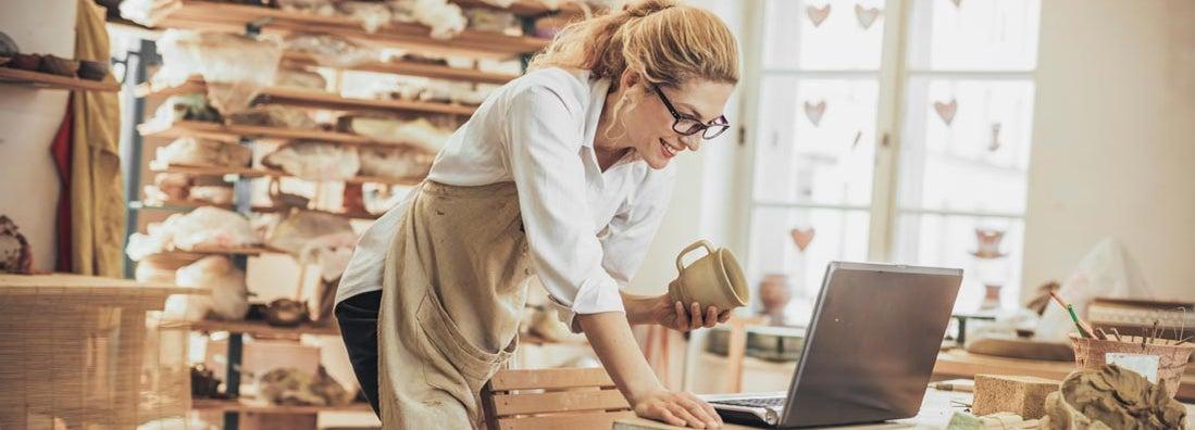 Potter entrepreneur using Shopify on laptop in workshop