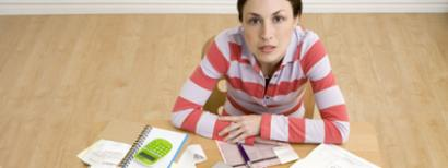 A woman going over paperwork looking stressed.