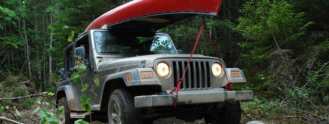 Traveling by Jeep 4x4 through a rough trail in the woods