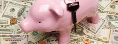 Piggy bank with a car key on top of money