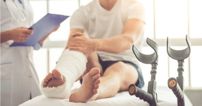 Medical doctor listening to patient with broken leg
