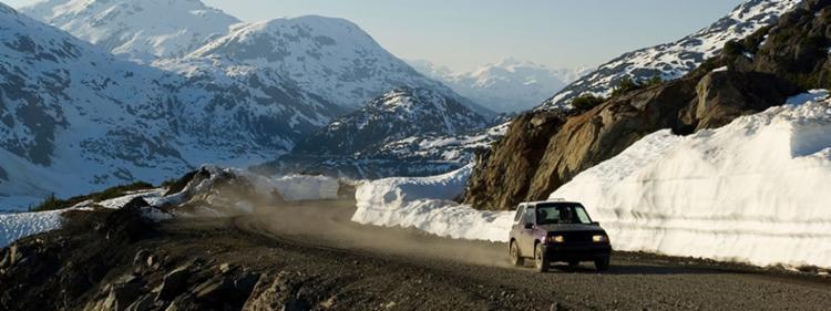 An SUV driving through epic mountainous terrain.