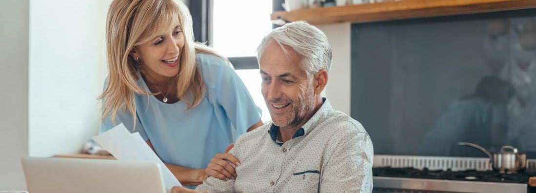 Mature couple smiling while calculating annuity interest rates together
