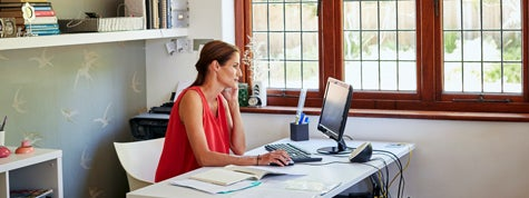 Woman using computer and mobile phone at desk in house