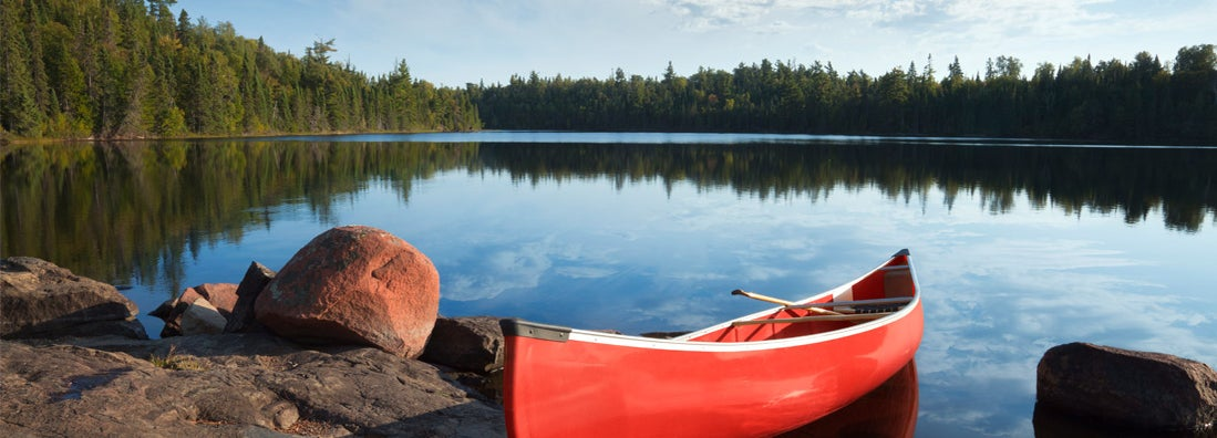 A red canoe rests on a rocky shore in the Boundary Waters of Minnesota