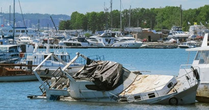 Sunken boat on the pier. Find vandalism to your boat at the marina.