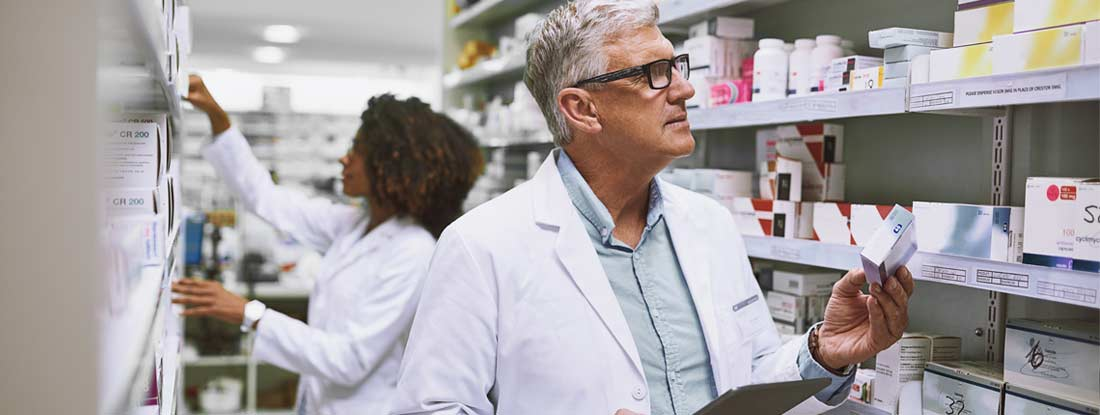 Male pharmacist getting medication from a shelf