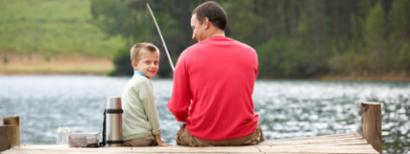Father and son fishing on a dock