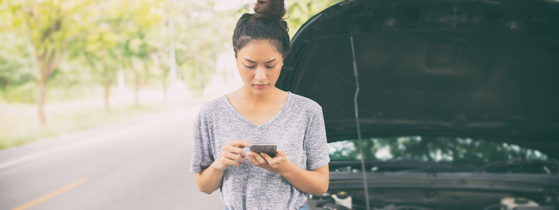 Woman using mobile phone after a car breakdown on street